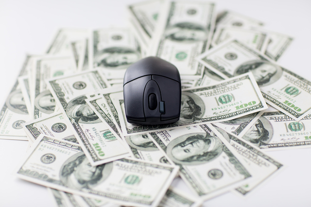 close up of computer mouse and dollar cash money